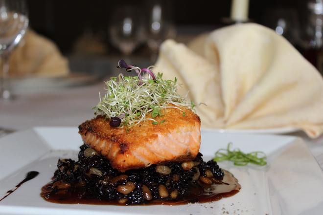 Филе от сьомга с хрупкава коричка върху черен ориз със стафиди и кедрови ядки