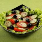 Салата от домати, краставици и маслини върху подложка от зелена салатка